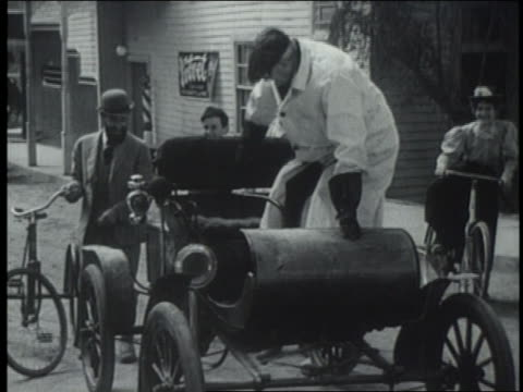 b/w reenactment 1890s/1900s man gets into car (horseless carriage) + drives away as others watch - 1890~1899年点の映像素材/bロール