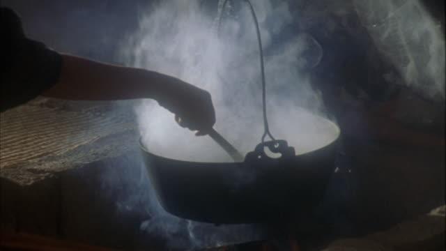 Reenactment close up woman stirring pot over open flame / Japan