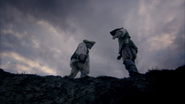 reenactment depicting two men throwing dead bodies into an open pit in paris in the 18th century. - epidemic stock-videos und b-roll-filmmaterial