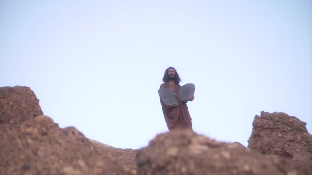 vídeos de stock, filmes e b-roll de a reenactment depicts abraham descending a hill with the ten commandments. - reconstituição histórica