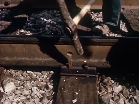 1963 Reenactment high angle close up nail being sledgehammered into railroad track / Texas / AUDIO