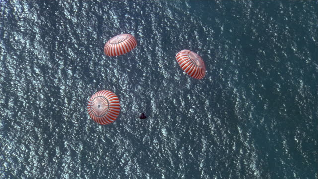 reenactment high angle long shot spacecraft module with parachutes floating towards ocean during splashdown - パラシュート点の映像素材/bロール