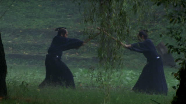 vídeos de stock e filmes b-roll de reenactment high speed wide shot two men fighting with sticks in kendo match / japan - samurai