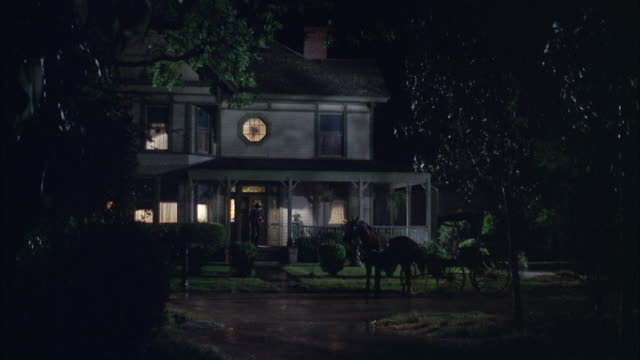 stockvideo's en b-roll-footage met 1966 ws reenactment man leaving victorian mansion and riding horse carriage at night - paardenkar