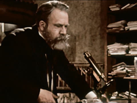 1953 reenactment medium shot Scientist Louis Pasteur looking through microscope / tracking shot rabbits in cage