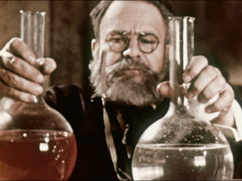 1953 reenactment medium shot scientist louis pasteur mixing clear and red chemicals in flask - 化学薬品点の映像素材/bロール