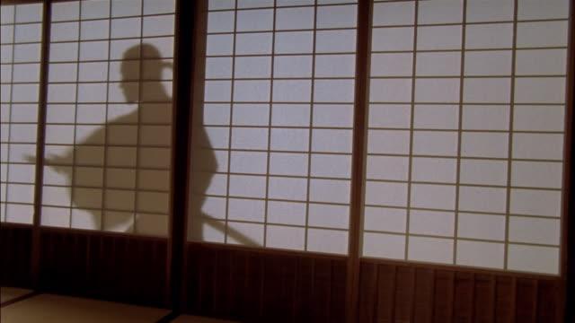 reenactment medium shot silhouette through shoji screen of samurai using katana / japan - samurai stock videos & royalty-free footage