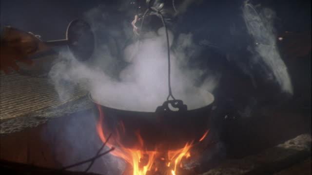 vídeos de stock e filmes b-roll de reenactment medium shot zoom in man removing lid from pot / woman stirring pot over open flame / japan - estilo do século 16