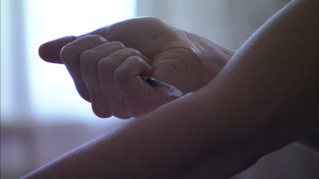a reenactment of a drug user injecting heroin into her arm. - injecting heroin stock videos & royalty-free footage