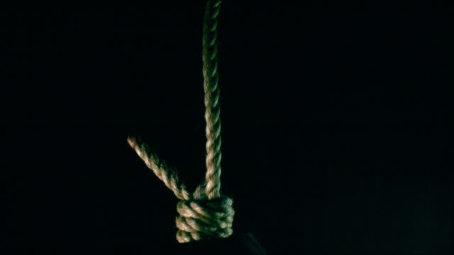 Reenactment of a person being with a rope noose dropping then focus of the rope pulling taught