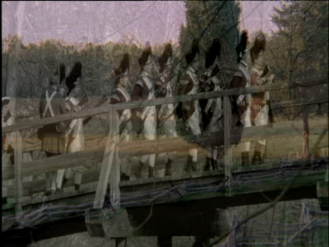 Re-enactment of British Redcoats marching across bridge during American War of Independence superimposed over trees in field