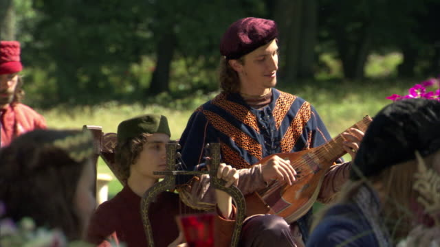 ms, selective focus, pan, reenactment of men playing lute and lyre at picnic outdoors, vilnius, lithuania - historische nachstellung stock-videos und b-roll-filmmaterial