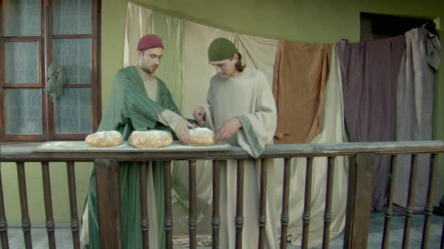 cs, ms, pan, reenactment of two men throwing bread loaves from balcony to man downstairs at medieval outdoor market, vilnius, lithuania - käfig stock-videos und b-roll-filmmaterial