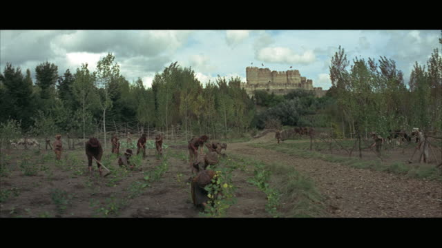 1966 ws reenactment peasants working on field and men horseback riding, castle in distance - medieval stock videos & royalty-free footage
