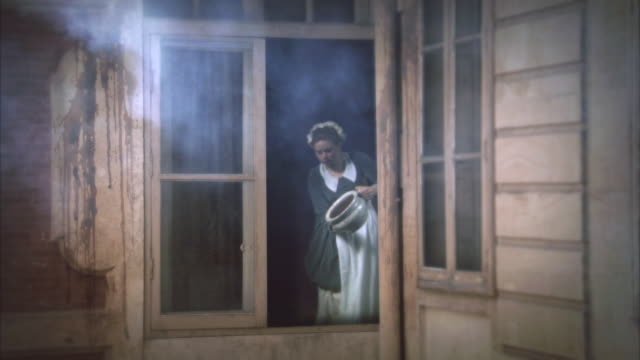 reenactment sequence depicting an 18th century maid emptying a chamber pot from a first floor window. - 18th century stock videos and b-roll footage