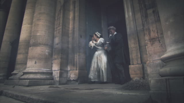 Reenactment sequence depicting an 18th century Parisian couple being confronted by piles of rotting bodies as they leave a church in the city.