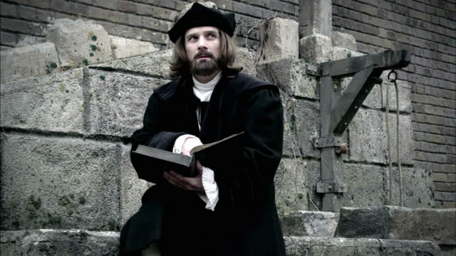a reenactment shows nostradamus studying outdoors. - stein baumaterial stock-videos und b-roll-filmmaterial