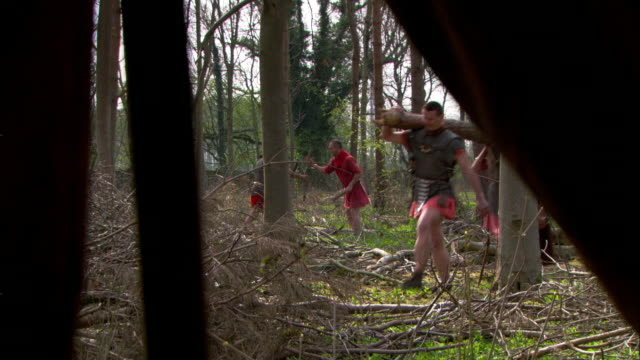 a reenactment shows roman soldiers carrying logs in the woods. - reenactment stock videos & royalty-free footage