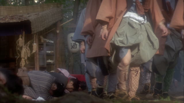reenactment slow motion medium shot peasants bowing on roadside as procession passes / japan - loyalty stock videos & royalty-free footage