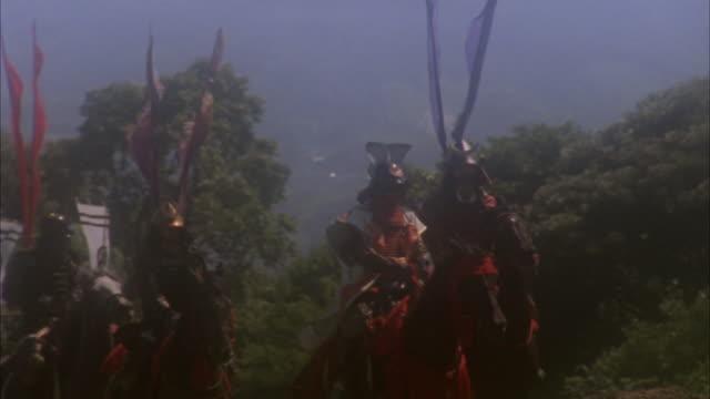 reenactment wide shot cavalry of samurai warriors riding in full battle regalia / japan - samurai stock videos & royalty-free footage