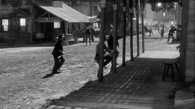 reenactment wide shot men scrambling for shelter and horses stampeding through old western town - stampeding stock videos & royalty-free footage