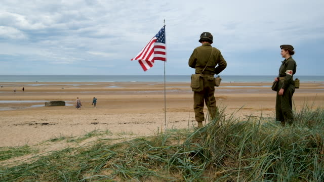 a reenactor wearing a us world war iiera military uniform snaps a photo of an american flag planted at omaha beach in normandy on june 02 2019 near... - omaha beach stock videos and b-roll footage