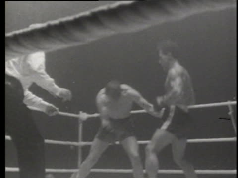 B/W referee and 2 men boxing in ring / 1 man falls / England / NO