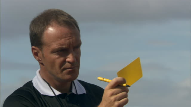 CU Referee blowing whistle and giving player a yellow card during soccer game/ Sheffield, England