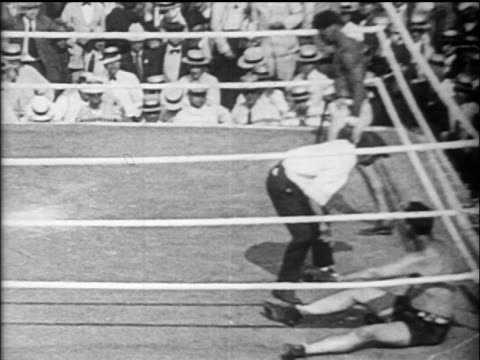 B/W 1919 referee counting as Jess Willard lies down / winner Jack Dempsey walking in background / Toledo