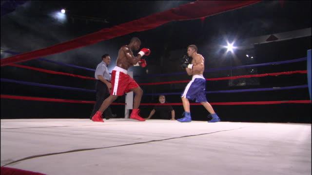 vídeos y material grabado en eventos de stock de la ws zi ms zo tu referee gesturing to two boxers in ring, then they fight while trainer watches ringside / jacksonville, florida, usa - guante de boxeo