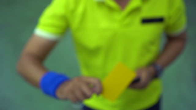 referee holds up yellow card : slow motion - football strip stock videos & royalty-free footage