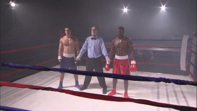 vídeos de stock, filmes e b-roll de sm ws referee raising winning boxer's arm and consoling other boxer after his defeat / jacksonville, florida, usa - posição de combate