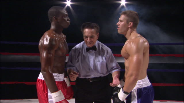MS Referee standing between two boxers facing off in ring / Jacksonville, Florida, USA