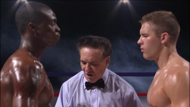 vídeos de stock, filmes e b-roll de cu td referee talking to two boxers facing off in ring / jacksonville, florida, usa - posição de combate