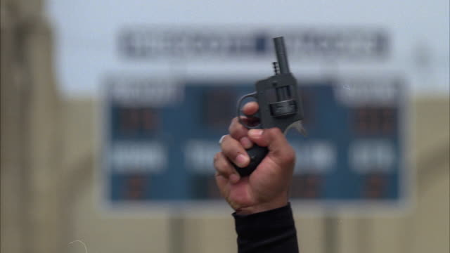 CU SELECTIVE FOCUS Referee's hand shooting starting pistol