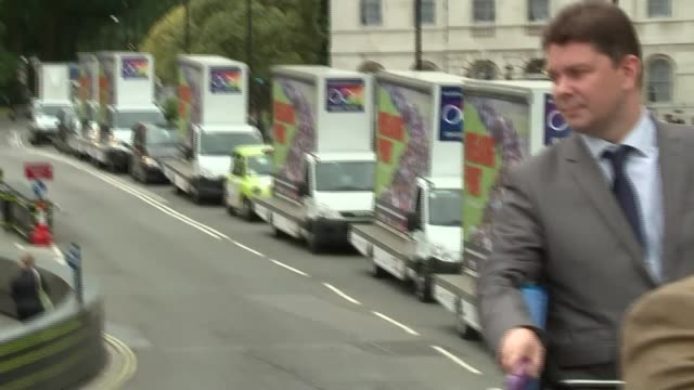 Nigel Farage poster van launch and bus tour of London Views of multiple poster trucks driving on road / along past Churchill statue and Big Ben /