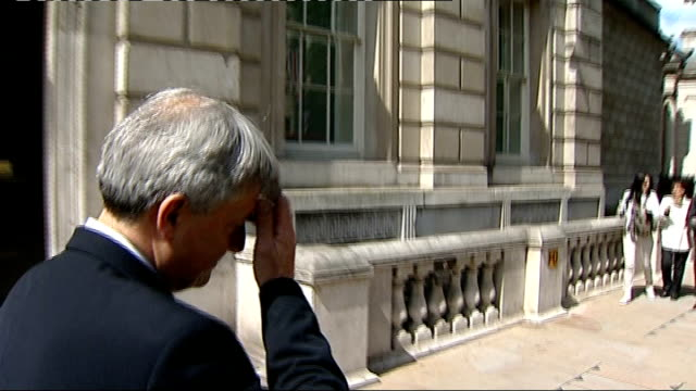 row at cabinet meeting; london: ext chris huhne along from cabinet office reporter to camera - クリス ヒューン点の映像素材/bロール
