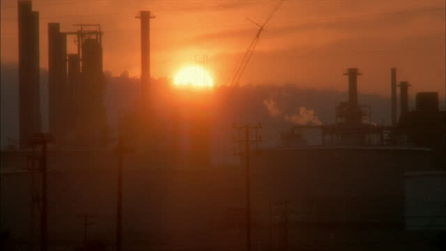 a refinery emits smoke from its smokestacks. - refinery stock videos & royalty-free footage