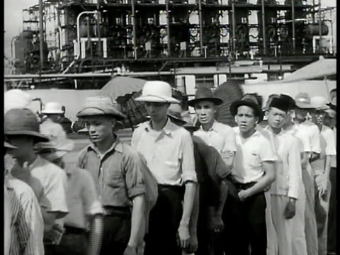 refinery tanks on hill large crowd of indonesian people outside building vs people standing in line men working in well area vs refinery tanks... - 1940 stock videos & royalty-free footage