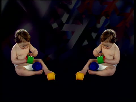 reflected image of toddler playing with plastic toys special effects to represent cloning - clonazione video stock e b–roll