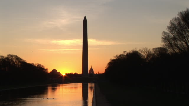 ws, reflecting pool and silhouette of washington monument against sky at sunset, washington dc, washington, usa - washington monument washington dc stock videos & royalty-free footage