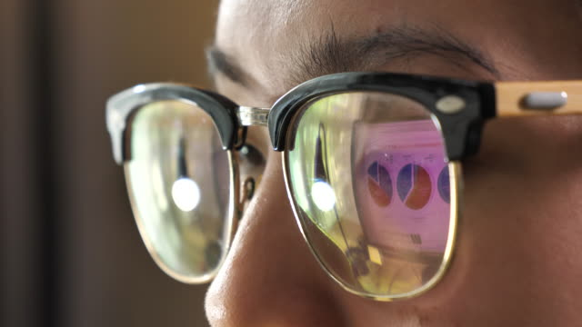 reflection business graphs on eyeglasses, looking at computer monitor - sorveglianza video stock e b–roll