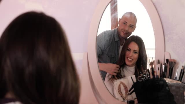 Reflexion in einem Spiegel des männlichen Friseur und seine zufriedenen Kunden.