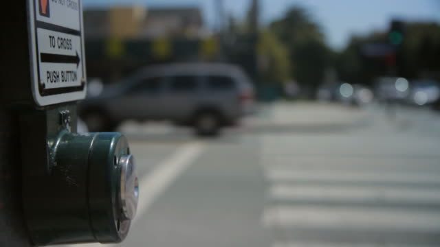 vídeos de stock, filmes e b-roll de reflection in crosswalk button - focus on foreground