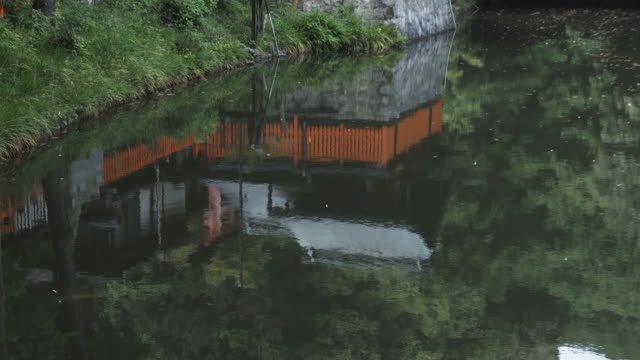 ms tu reflection in lake surface and buildings at fushimi inari taisha shrine, kyoto, japan - shrine stock videos & royalty-free footage