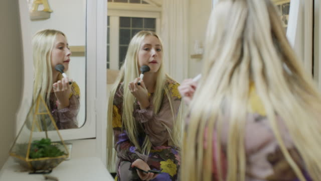 reflection in mirror of girl applying makeup to face with brush / highland, utah, united states - only teenage girls stock videos and b-roll footage
