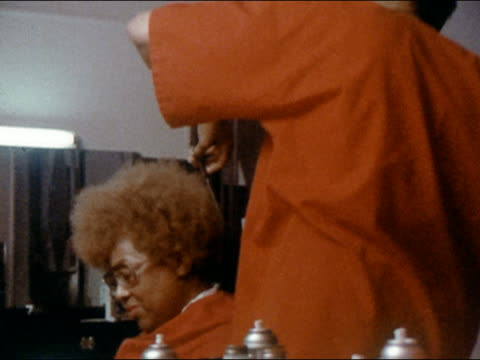 1970 reflection in mirror of woman with red afro getting trim in salon / zoom out medium shot pan to woman and stylist - afro stock videos & royalty-free footage