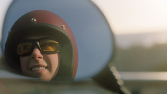 ecu slo mo. reflection in rearview mirror as young woman in motorcycle helmet looks around at beautiful day. - スポーツヘルメット点の映像素材/bロール