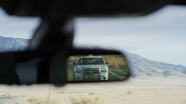 reflection in rear-view mirror of police car pulling over driver / eagle mountain, utah, united states - following stock videos & royalty-free footage