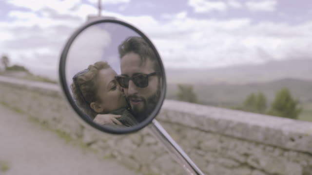 reflection in side mirror of couple kissing - turista video stock e b–roll